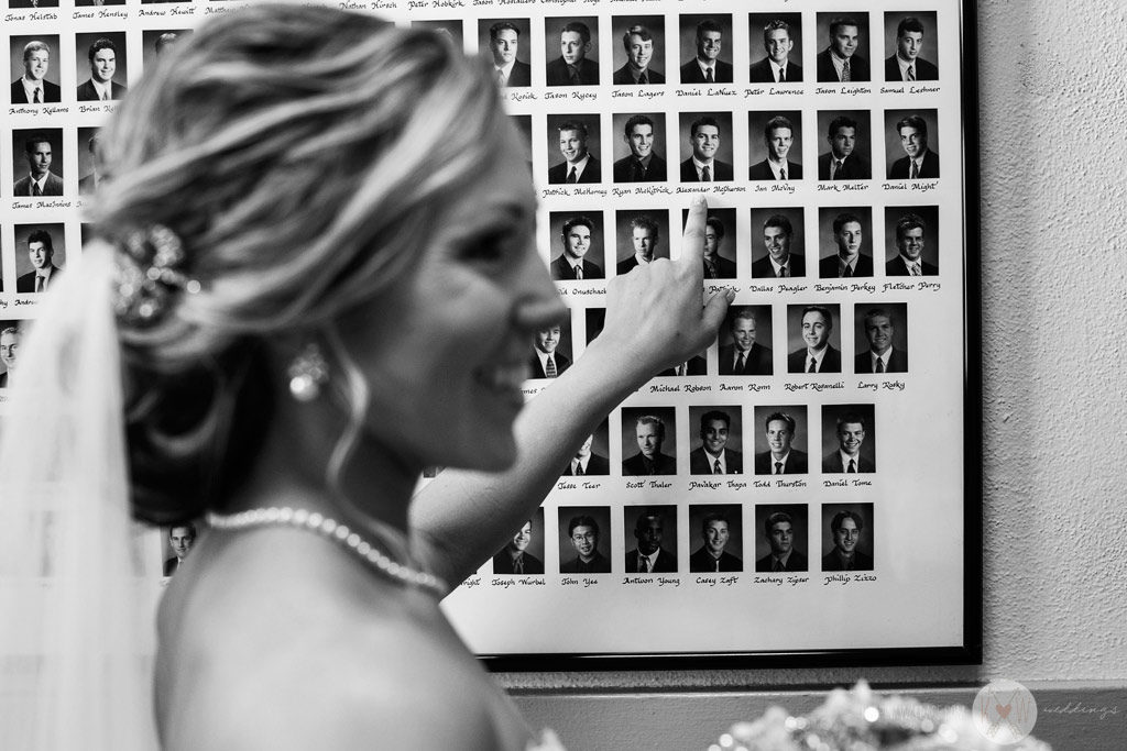 The bride points out her groom's portrait on the wall at Brophey Chapel just before the ceremony