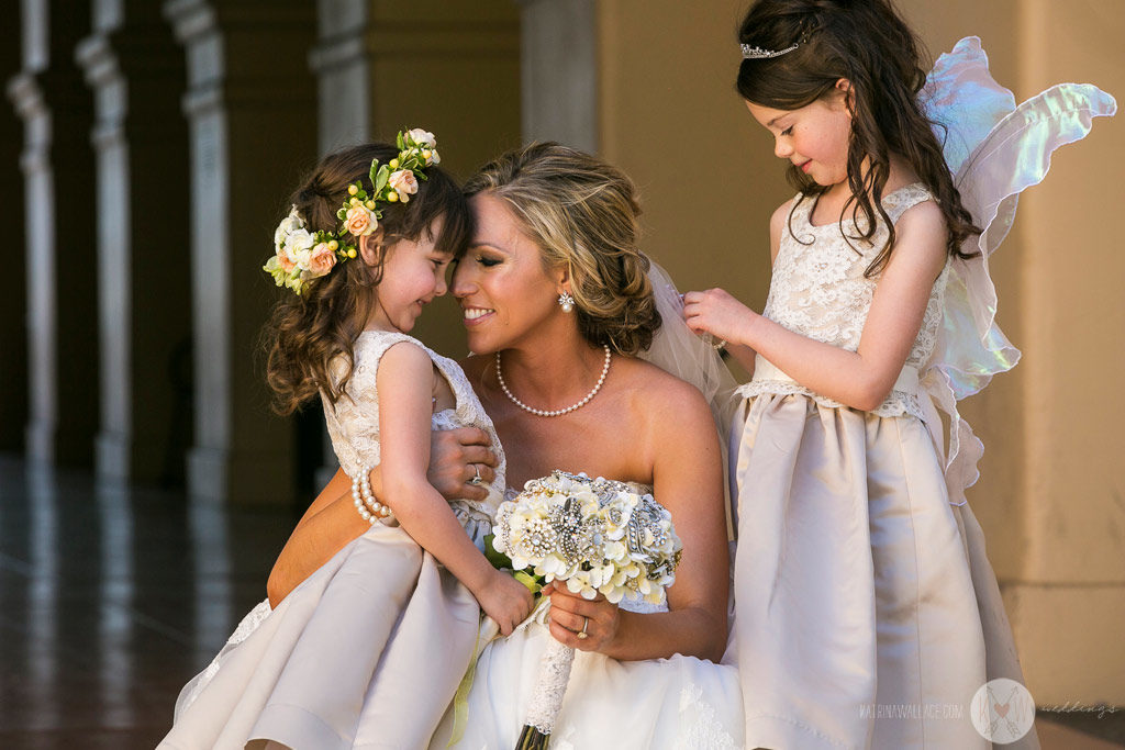 The bride share a hug and a kiss with the flower girls just before the Brophey Chapel ceremony