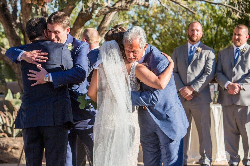 The Dads hug the bride and the groom as the ceremony begins.