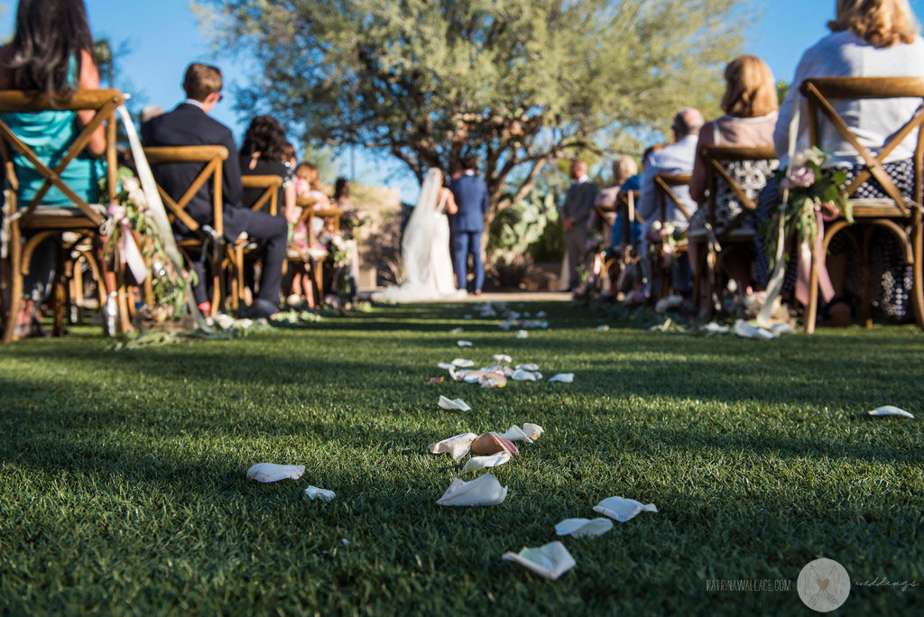 A view down the aisle from the grass, with flower petals carpeting the path.
