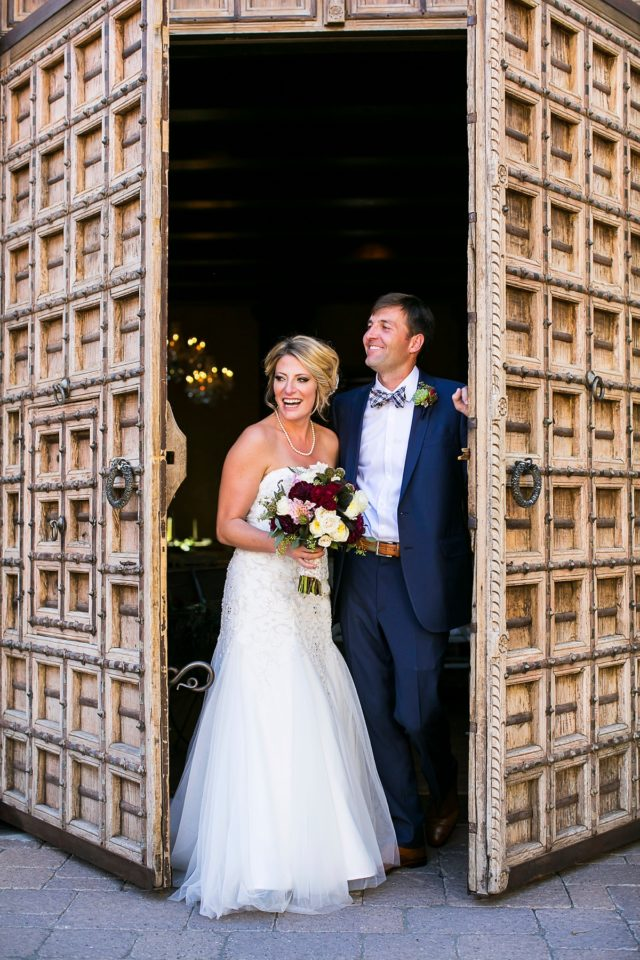Montelucia wedding photo of a bride and groom laughing infront of the wooden doors at Montelucia