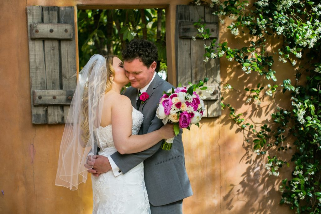 Royal Palms wedding photographer couple embracing on their wedding day in front of a wooden window frame